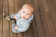 stock-photo-63511629-baby-sitting-on-the-floor-and-looking-at-the-camera